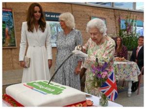 Queen Elizabeth II cuts a cake with a sword